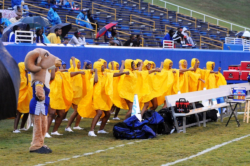 Albany State mascot and cheerleaders cheer in the rain
