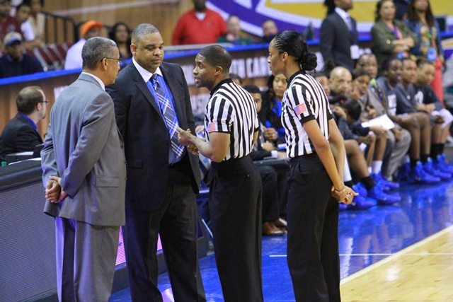 Referee's talk to Hampton and Coppin basketb...