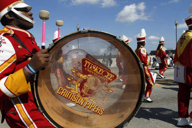 Tuskegee Crimson Pipers drummers march in the par...